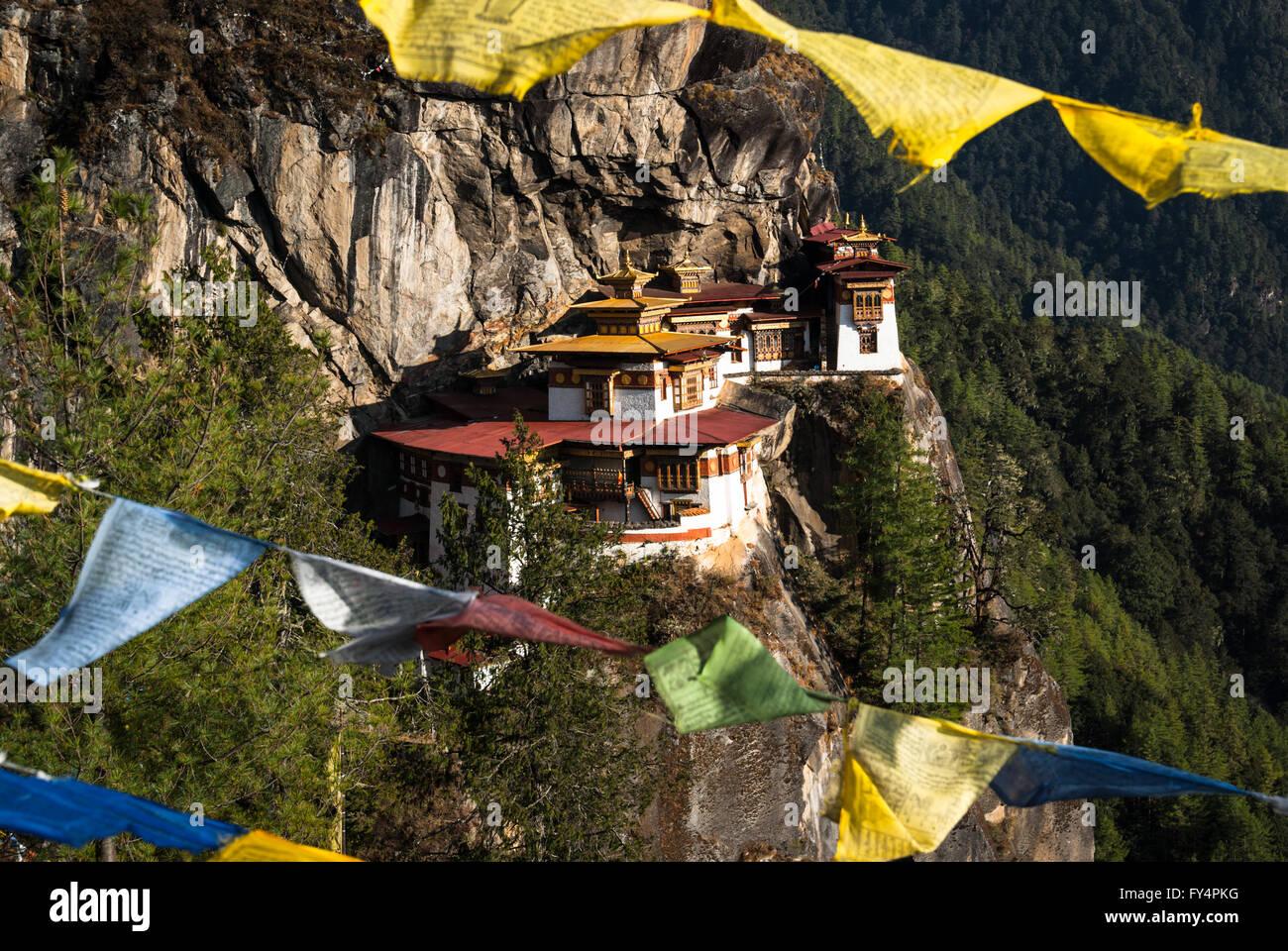Vista entre banderas de oración a Tiger's Nest (Monasterio de Taktshang), encaramado sobre un acantilado cerca de Paro, Bhután Foto de stock