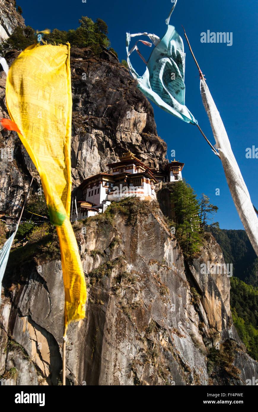 Ver a través de la oración banderas a Tiger's Nest (Monasterio de Taktshang), encaramado sobre un acantilado cerca de Paro, Bhután Foto de stock