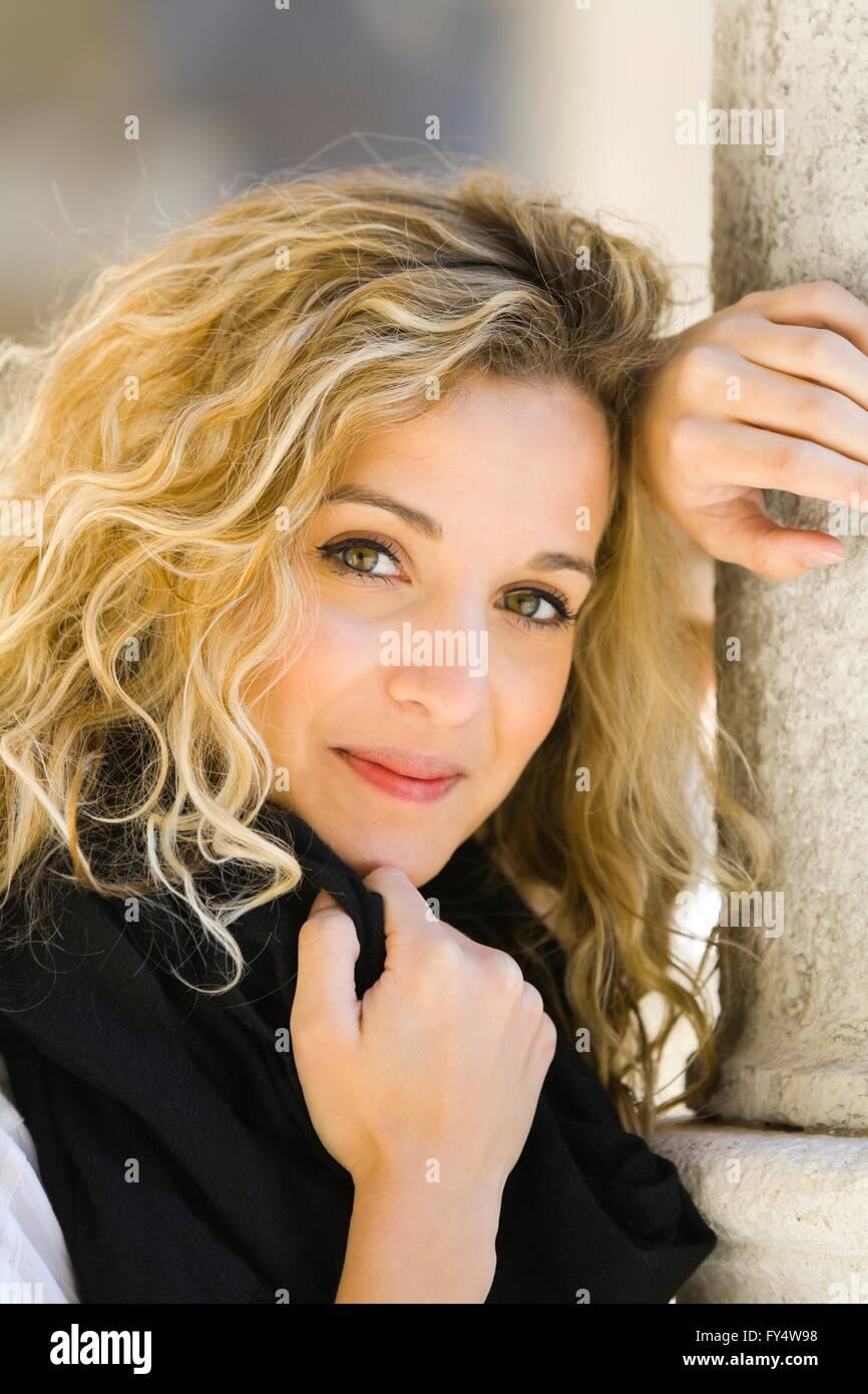 Atractiva joven mujer en Negro retrato pelo rizado rubio inclinado sonrisa sonriente sensación positiva humor rizos Foto de stock