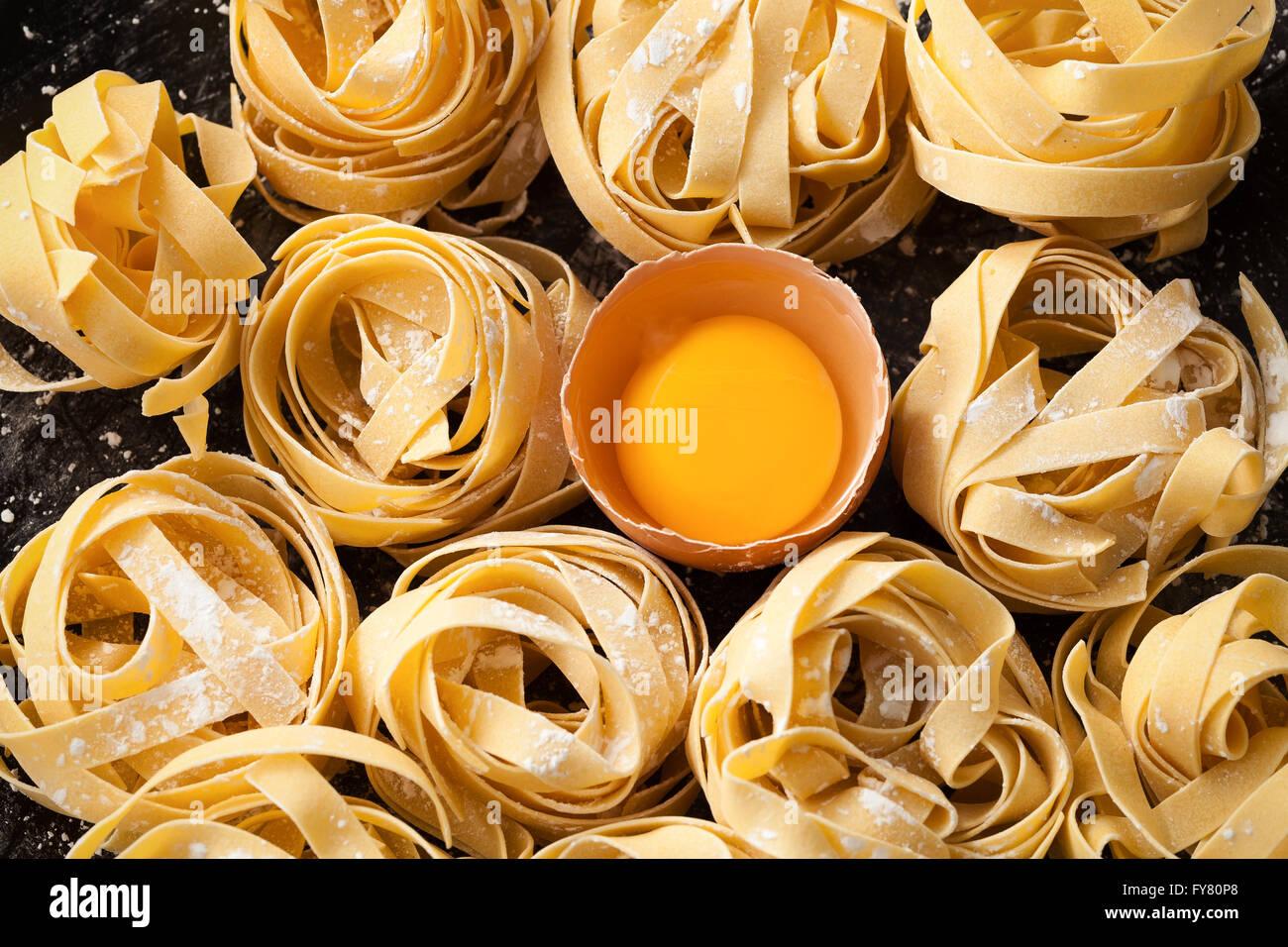 Comida italiana pasta fettuccine bodegón rústico laicos plana fondo negro tagliatelle alfredo yema macro Imagen De Stock