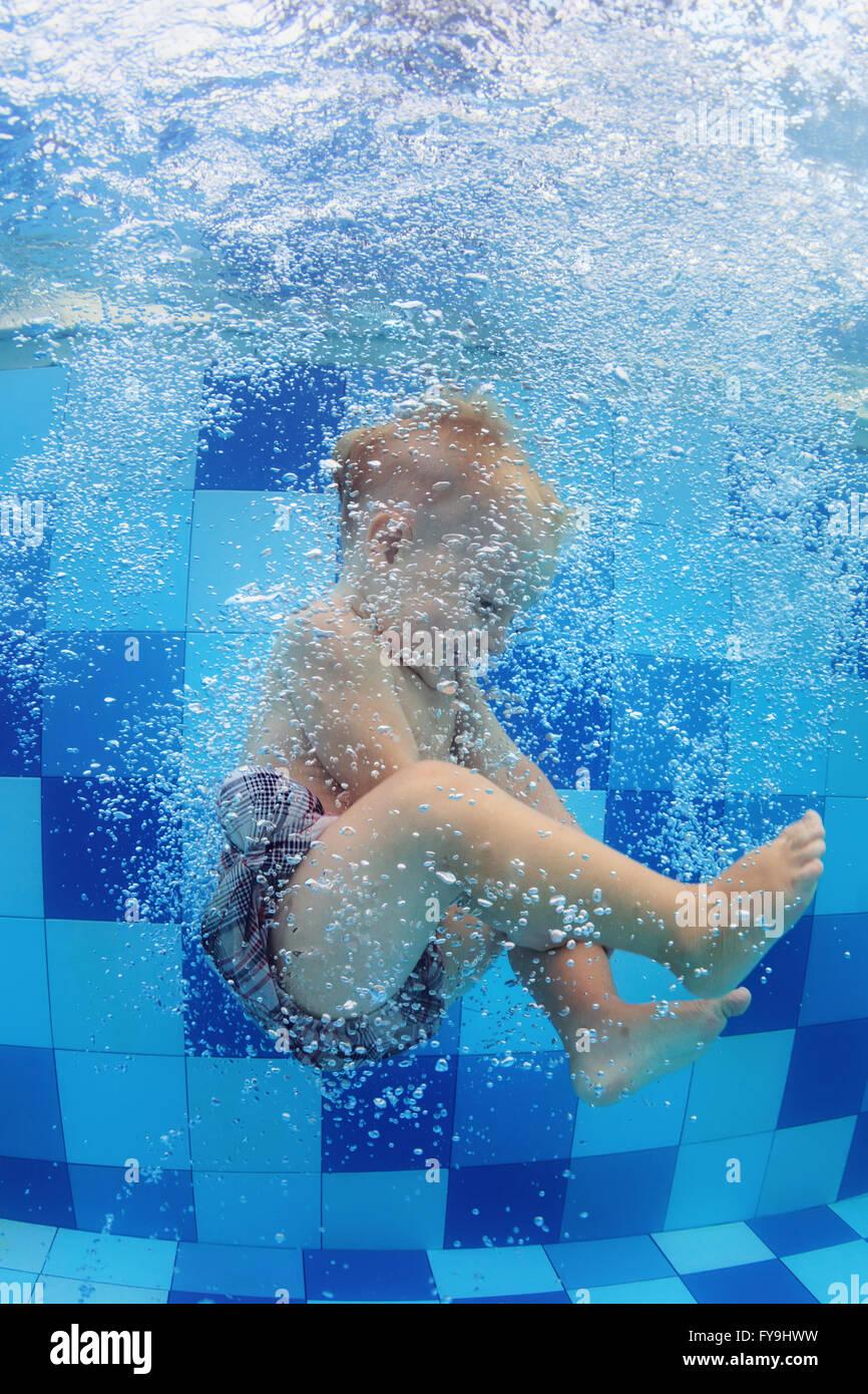 Gracioso foto de Baby Boy nadar y bucear en la piscina con la diversión - saltar profundo subacuático Imagen De Stock