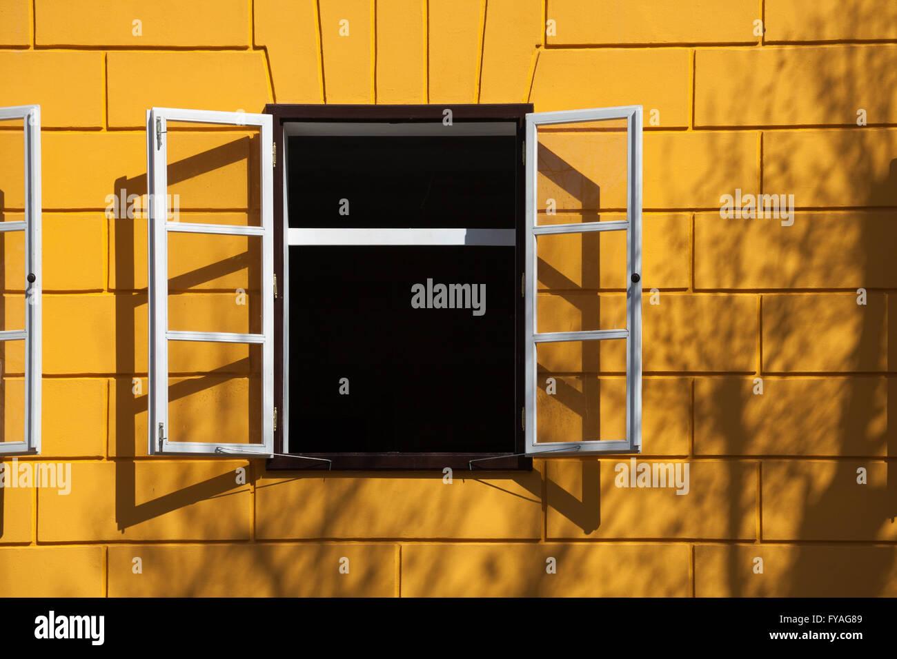 Abrir ventana con marcos blancos, ladrillos amarillos y algunas ...