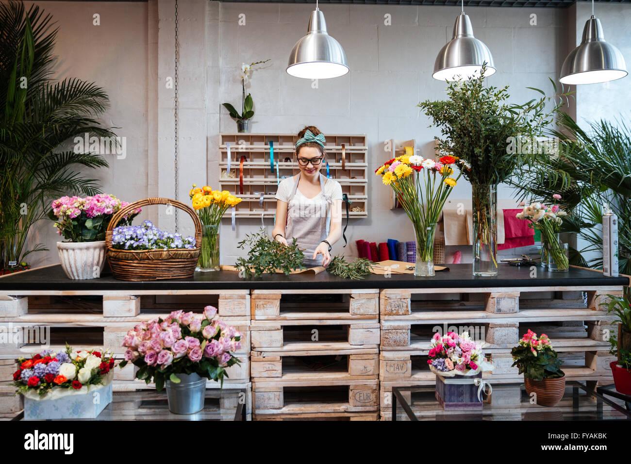 Sonriente joven mujer atractiva florista de pie y trabajando en flower shop Imagen De Stock
