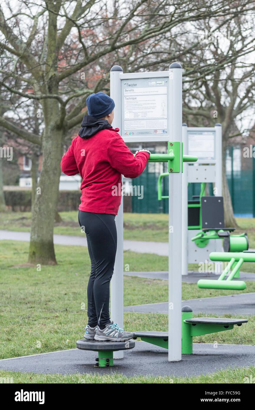 Mujer con máquina de ejercicio en parque público. Inglaterra. UK Imagen De Stock