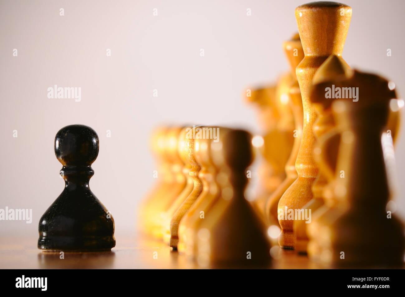 Peón negro contra el blanco ejército de piezas de ajedrez Imagen De Stock