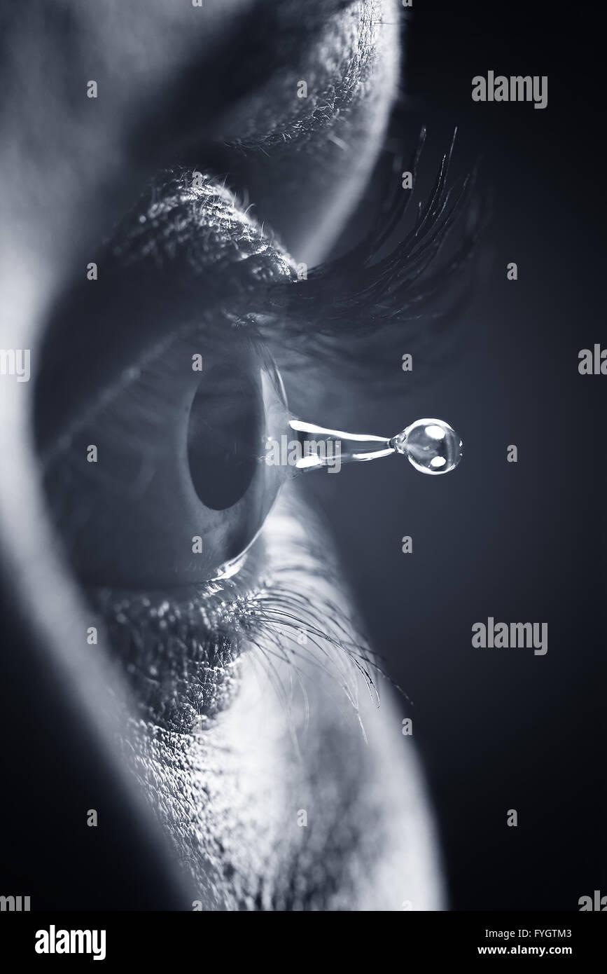 Concepto de visión y salud ocular. Detalle de la pupila y desgarro de la gota de agua Imagen De Stock