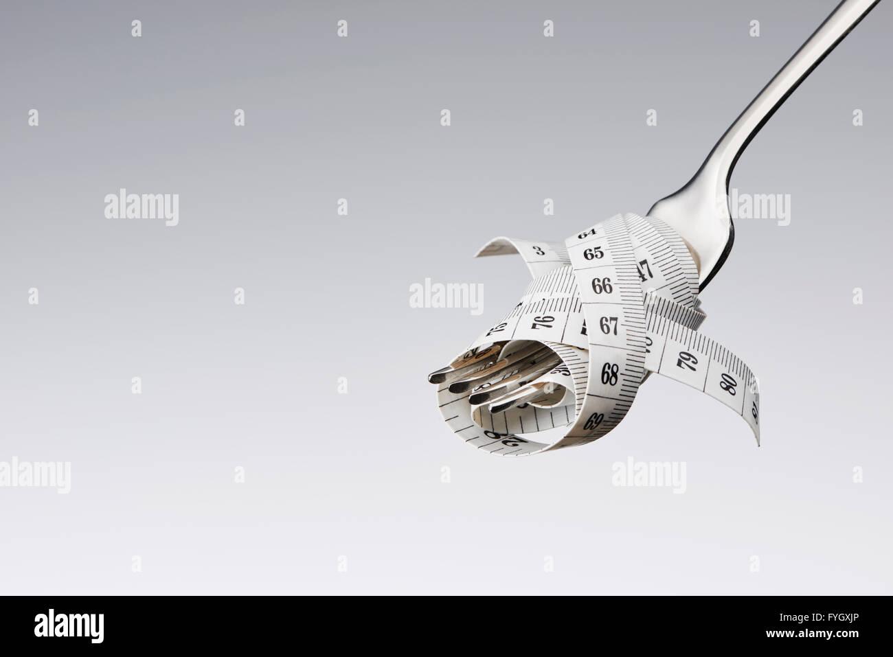 Horquilla con cinta métrica, adietando concepto Obesidad Imagen De Stock