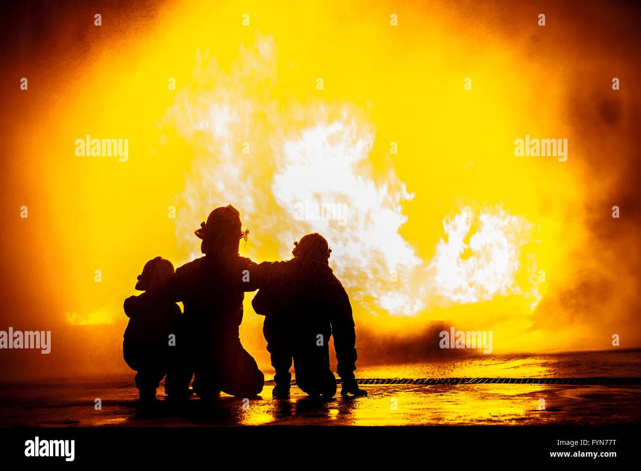Los bomberos delante de un tanque ardiendo Foto de stock