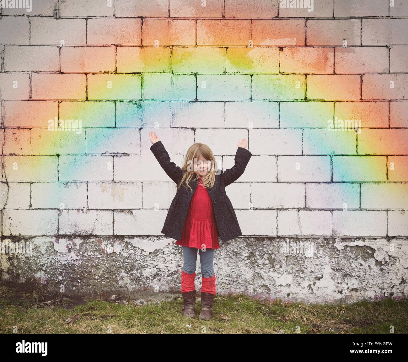 Una niña feliz está de pie contra una pared de ladrillo antiguo con un arco iris de colores y sus manos Imagen De Stock