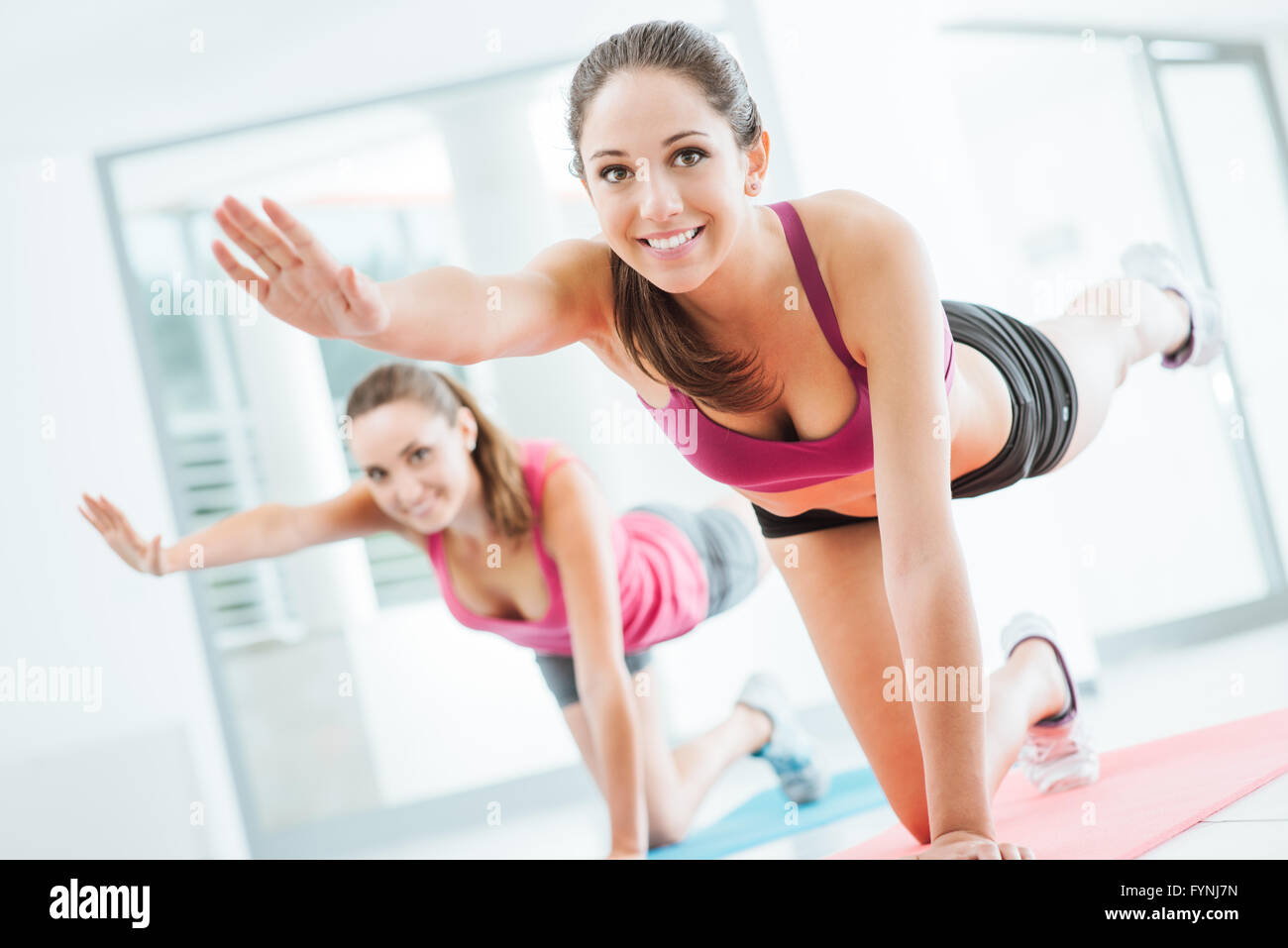 Las mujeres jóvenes deportistas en el gimnasio haciendo pilates sobre una estera, fitness y concepto de estilo Imagen De Stock