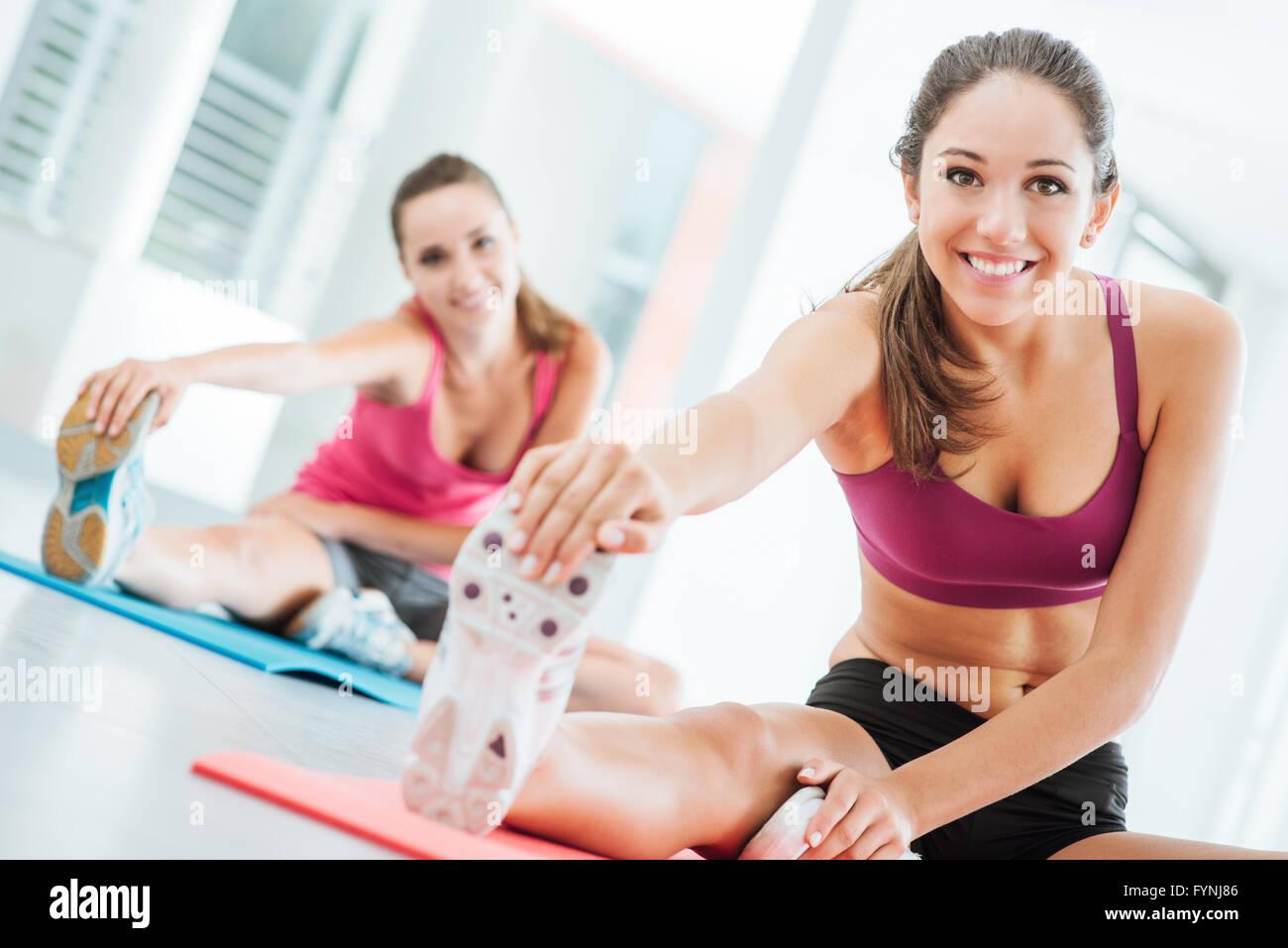Sonriente joven mujer en el gimnasio haciendo un ejercicio de estiramiento para las piernas sobre una estera, concepto Imagen De Stock