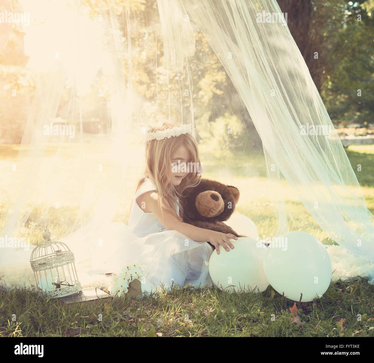 Una preciosa chica está jugando con globos en un vestido blanco fuera bajo un dosel con la luz del sol de primavera Imagen De Stock