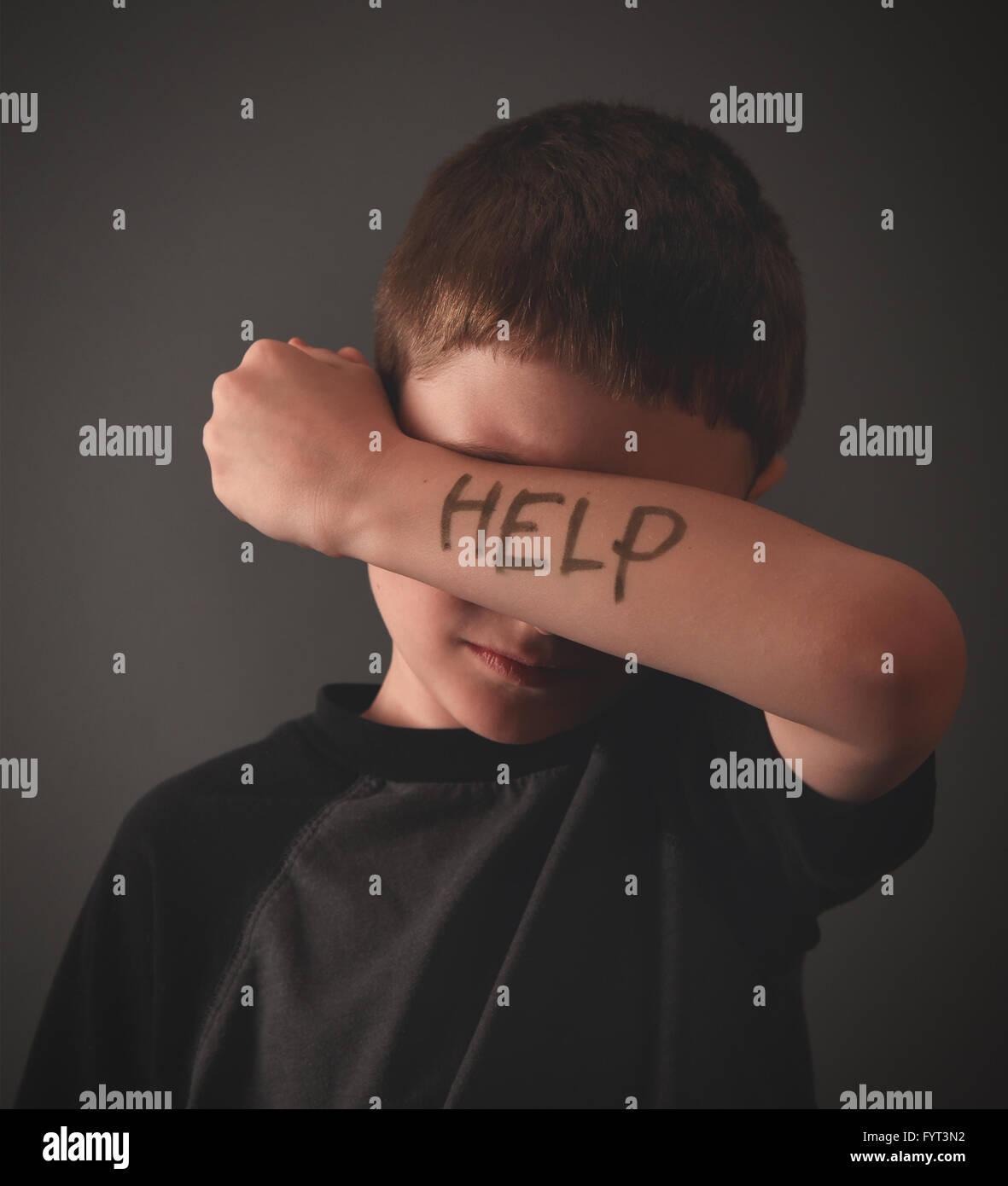 Un niño está ocultando sus ojos con un mensaje escrito de ayuda en su brazo para un problema social, bully o tristeza Foto de stock