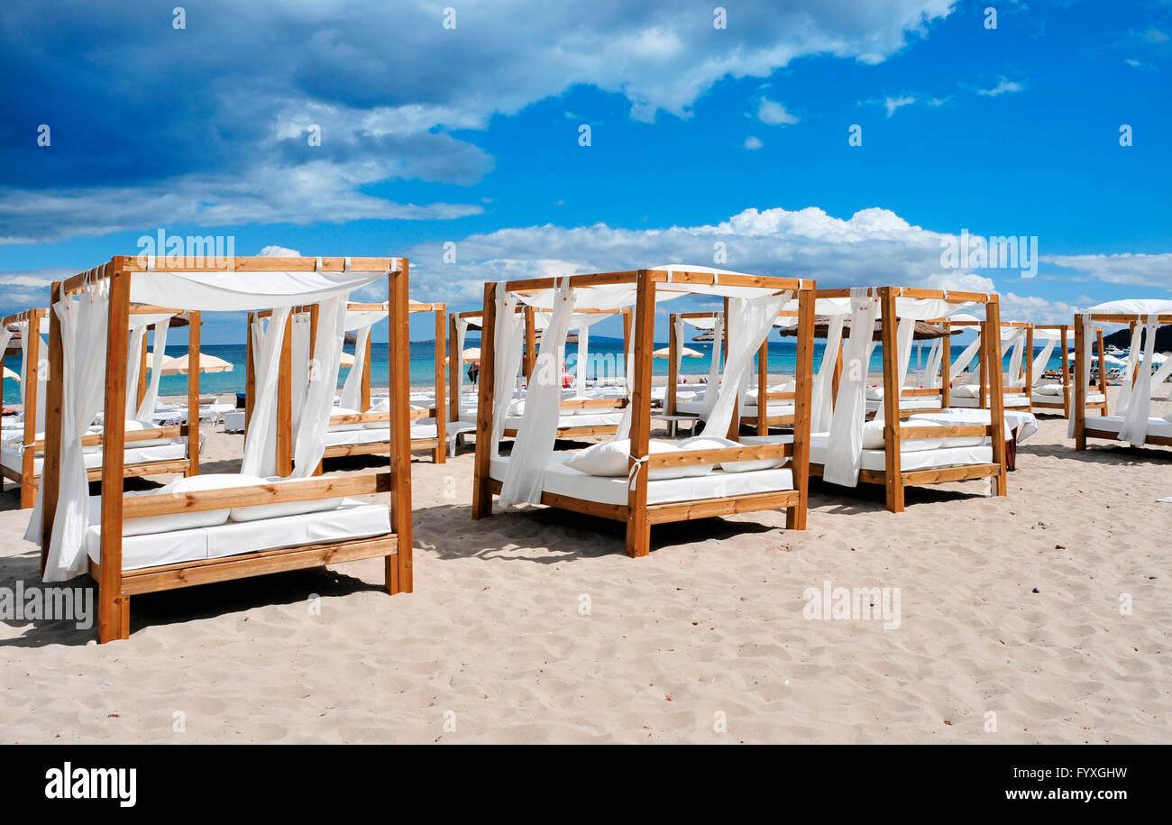 Algunas camas y tumbonas en un club de playa en una playa de arena blanca en la isla de Ibiza, España Imagen De Stock