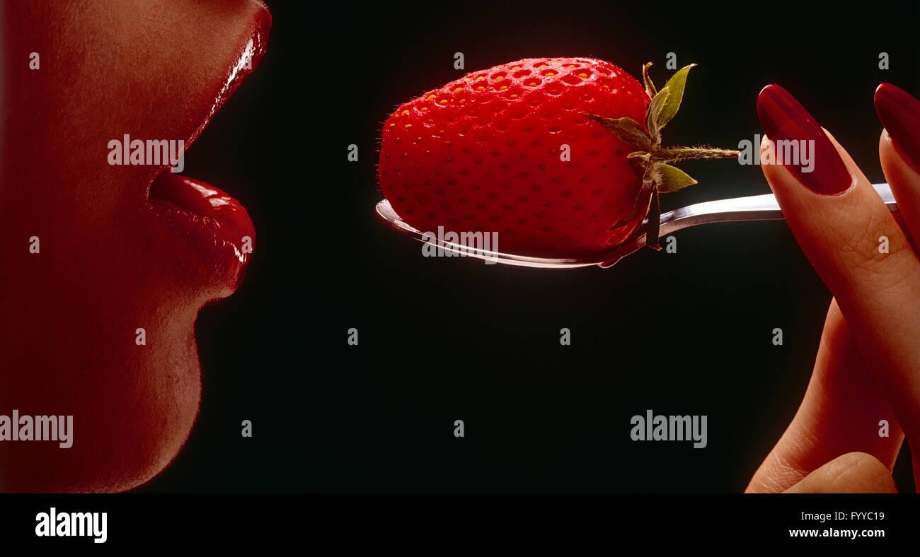 Una fresa en una cuchara se colocan en un niñas boca, adentro. Foto de stock
