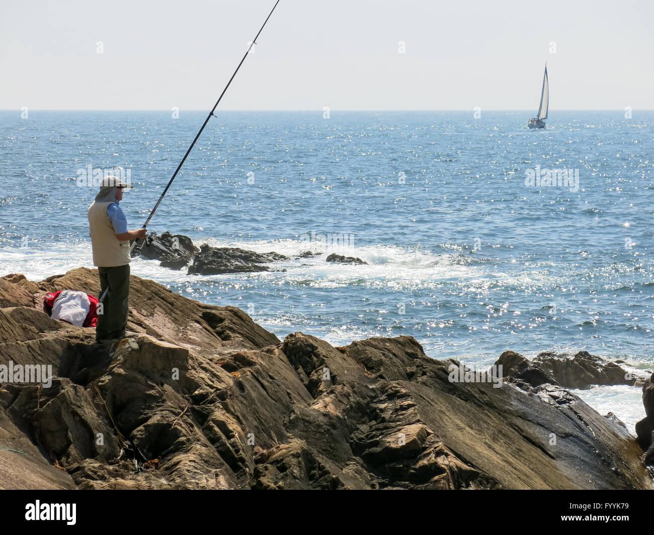 Pescador pesca en el Océano Atlántico y el velero navegando en el mar frente a la costa de Foz cerca de Porto, Portugal Foto de stock