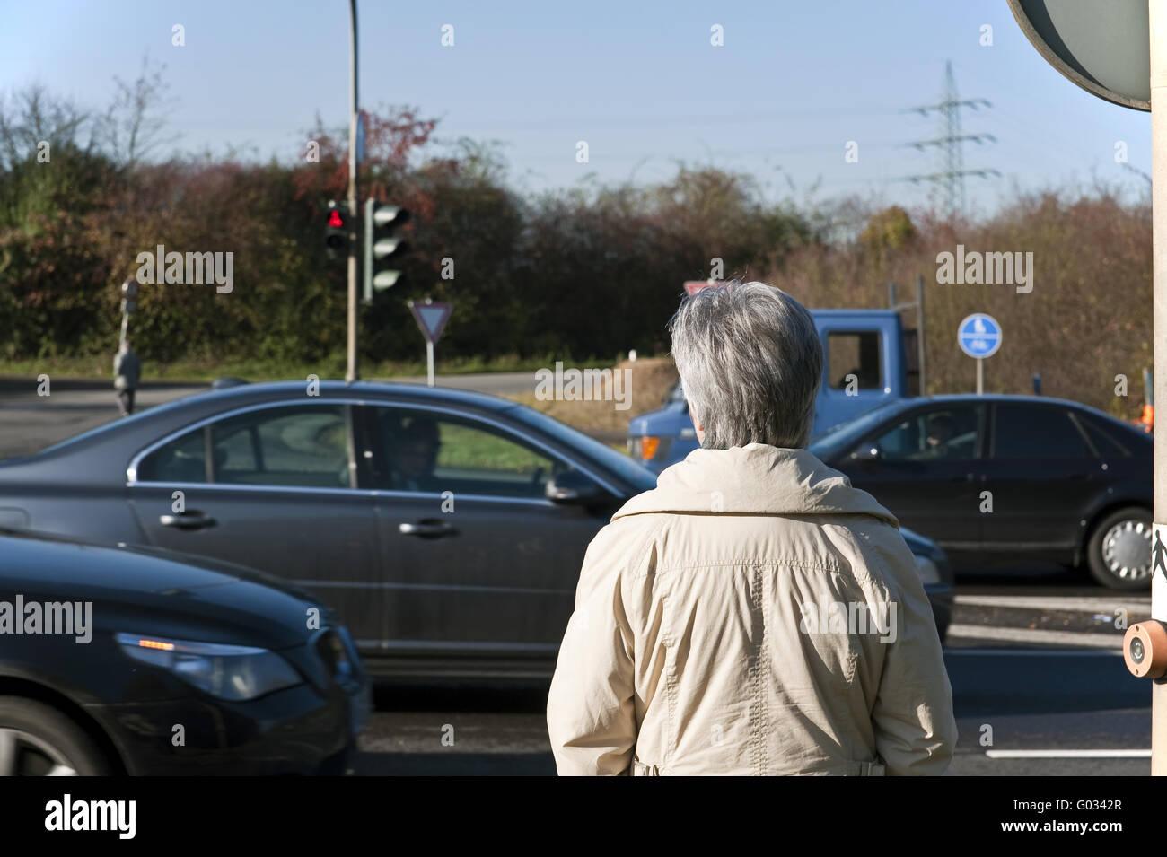 Mujer de pie en una calle que cruza con luz roja Imagen De Stock