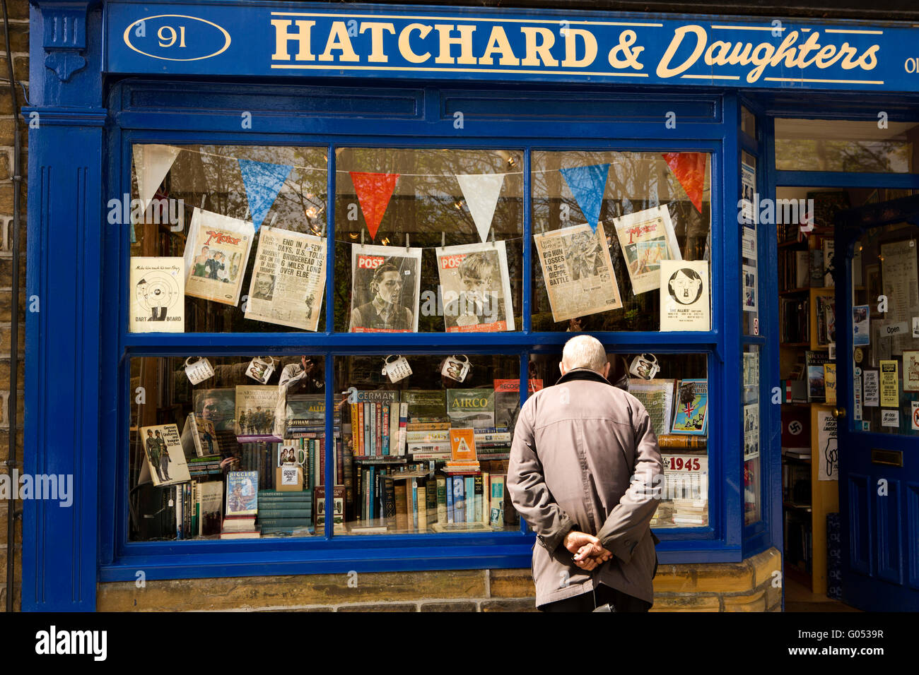 Reino Unido, Inglaterra, Yorkshire, Haworth 40s el fin de semana, Calle Principal, visitante mirando en la ventana Imagen De Stock
