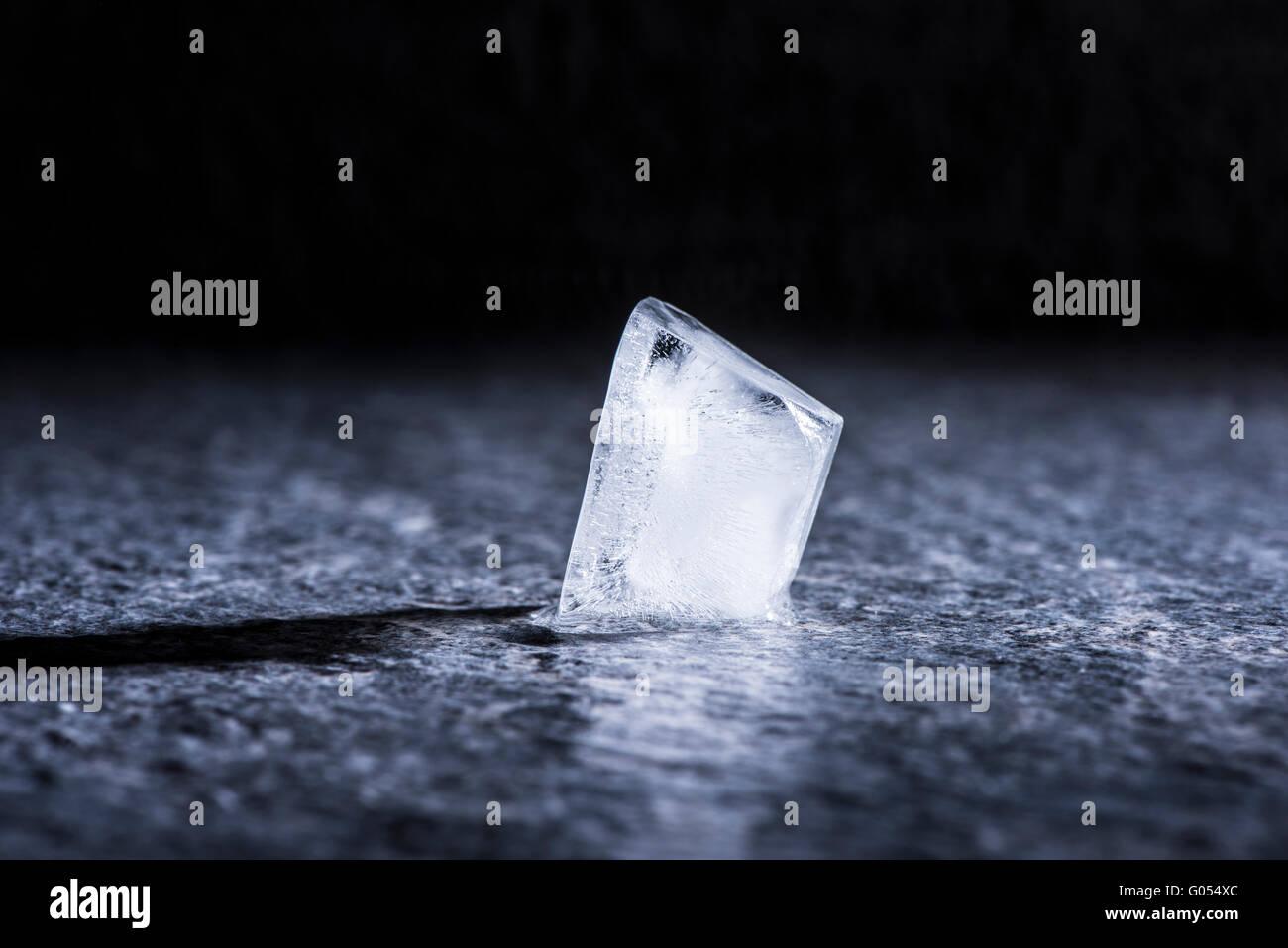 Cubo de hielo en fusión de cerca. Concepto de temperatura fría, agua y cambio. Imagen De Stock