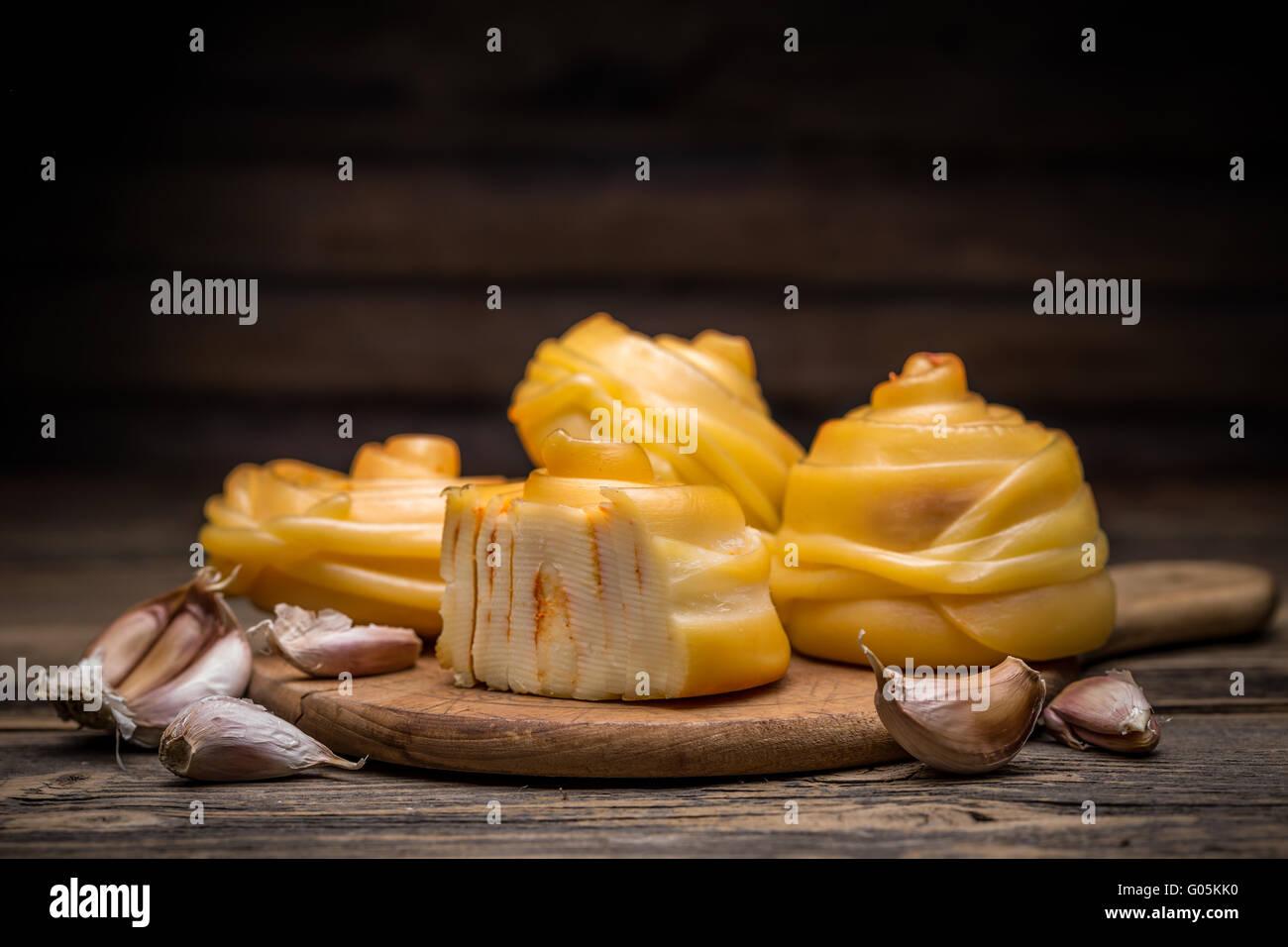 Queso artesanal trenzado sobre tablero de madera Foto de stock