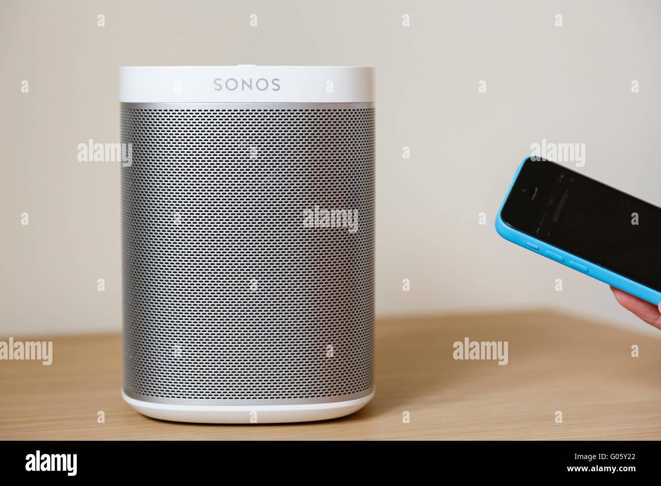 Persona que utiliza un controlador de iPhone app para controlar la música desde un inalámbrico SONOS Play Imagen De Stock