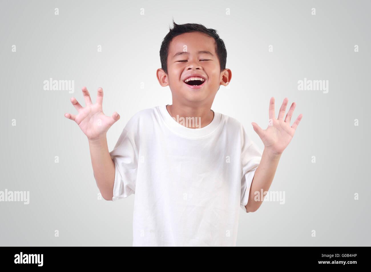 edb4f7b235 Retrato de niño en Asia feliz con pelo negro vistiendo franela blanca riendo  y aumentando sus