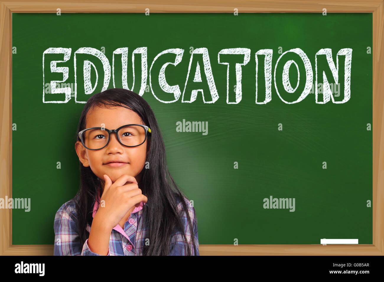 Estudiantes Asiáticos poco chica sonriente y pensando en pizarra verde con educación escrito en Word Imagen De Stock
