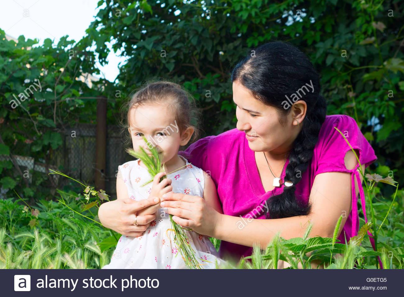 Madre e hija jugando en el campo, sentados en Imagen De Stock