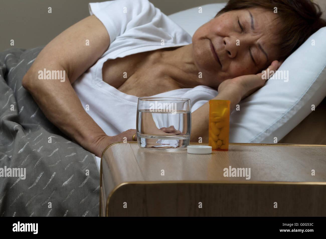 Botella de medicamentos y agua con altos mujer durmiendo en segundo plano. Foto de stock