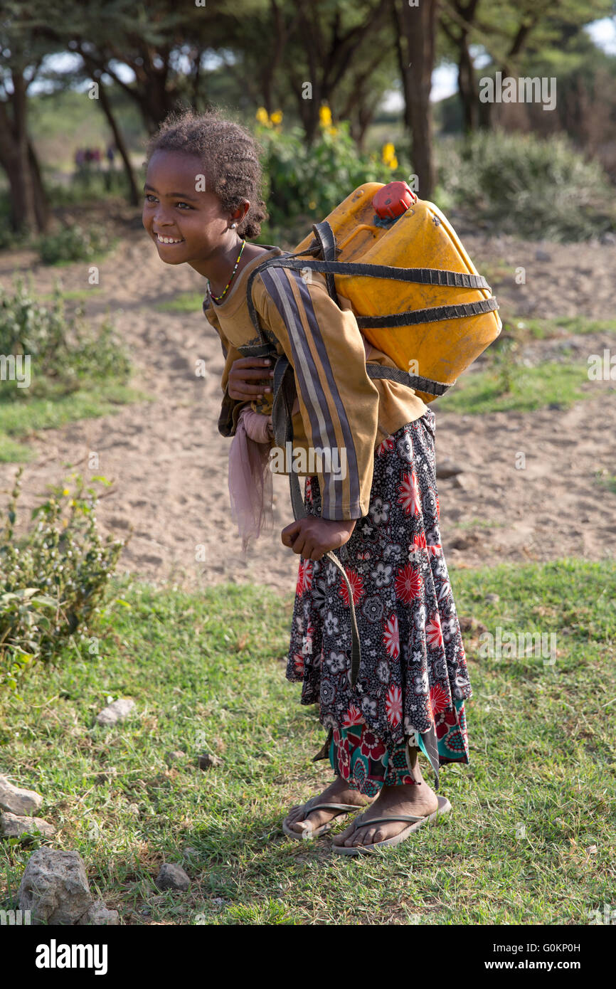 El lago Langano, Etiopía, de octubre de 2013 Lomi Aman, 9, lleva agua 1.5km casa todos los días. Ella Imagen De Stock