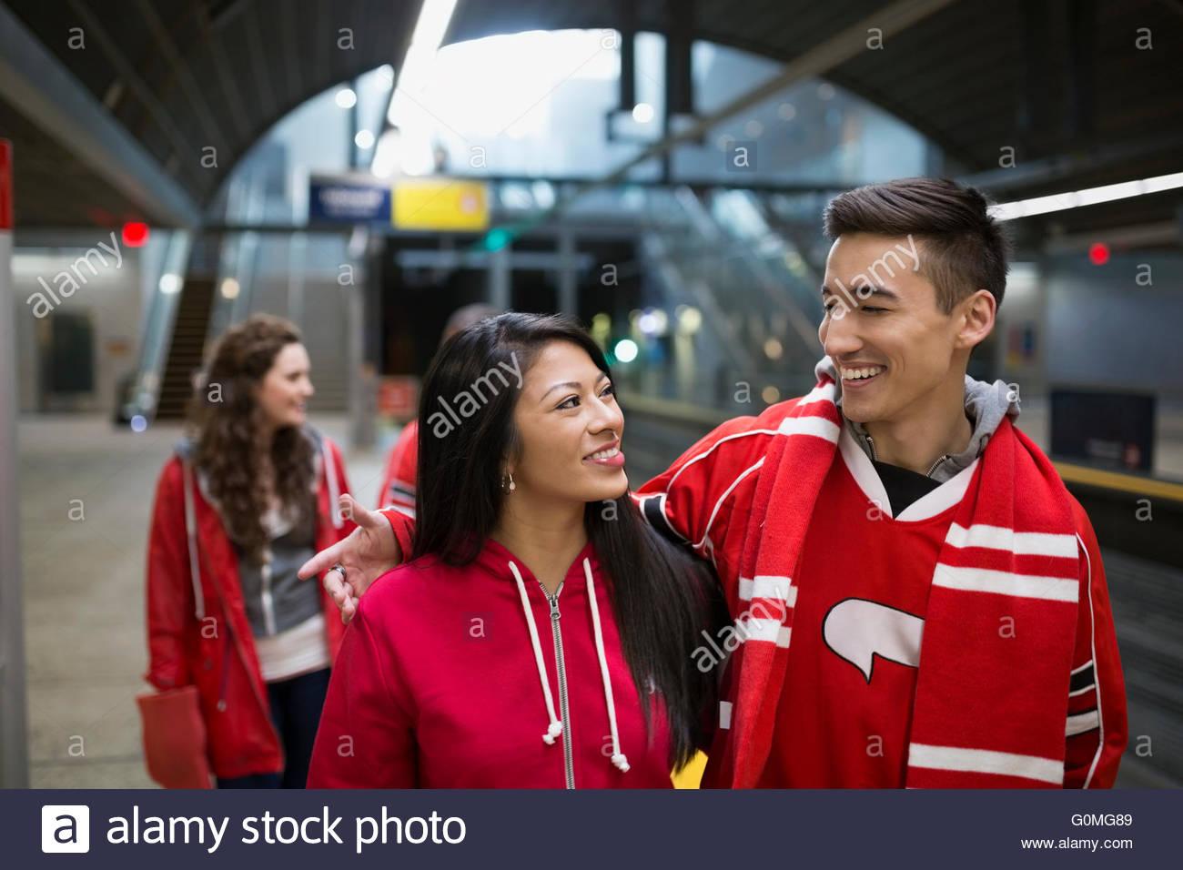 Los fanáticos de los deportes par rojo abrazando a estación de metro plataforma Imagen De Stock