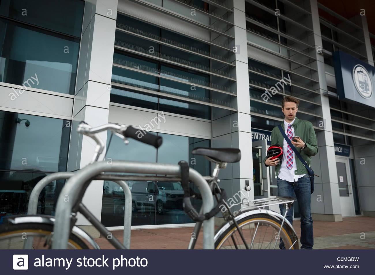 Empresario acercando a bicicleta fija a post Imagen De Stock