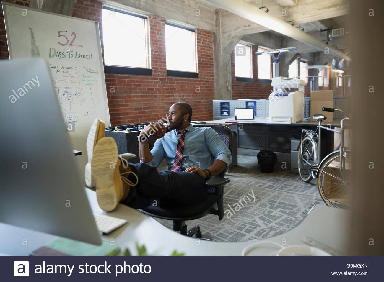 Empresario con los pies para arriba en la nueva oficina de escritorio Imagen De Stock