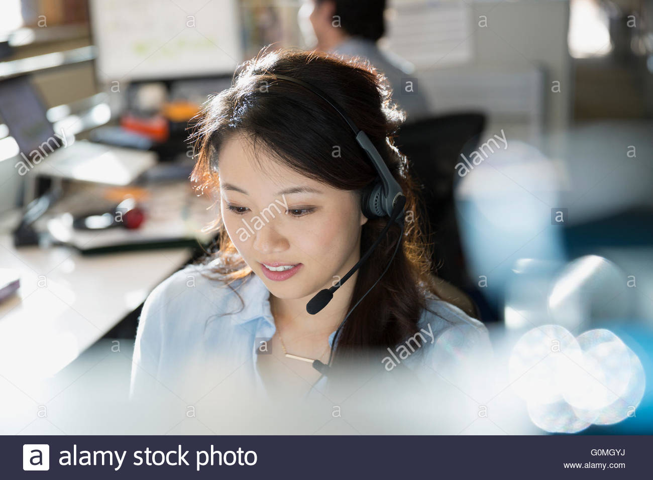 La empresaria vistiendo los auriculares en un escritorio en la oficina Imagen De Stock