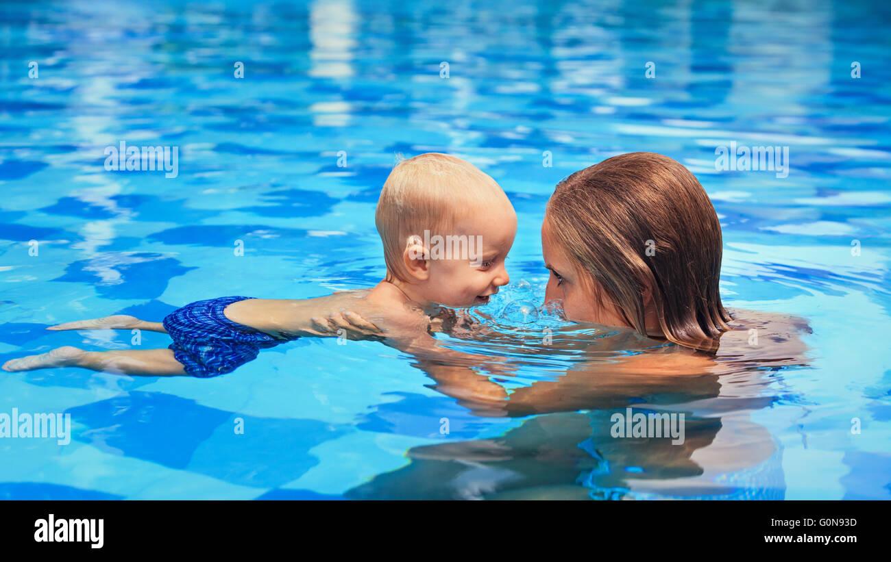 Deportes poco feliz el hombre ha lección de natación con la madre - bebé activo divertido nadar con Imagen De Stock