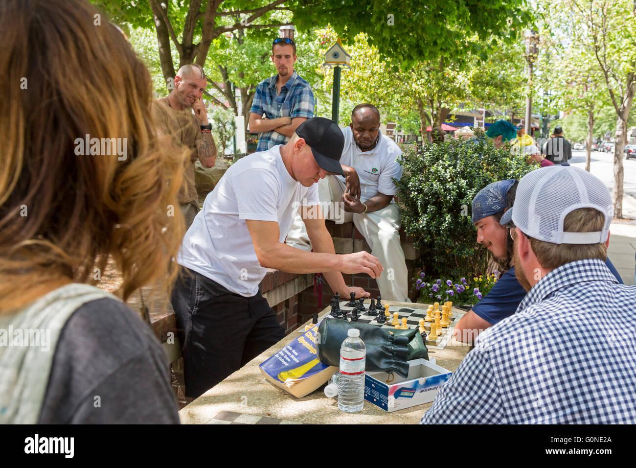 En Asheville, Carolina del Norte - El actor Woody Harrelson (tapa negra) juega ajedrez en Pritchard Park. Muchos Imagen De Stock