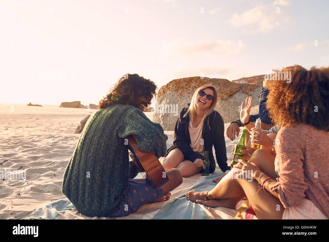 Retrato de joven tocando la guitarra para los amigos. Grupo de Amigos divirtiéndose en la fiesta en la playa. Imagen De Stock