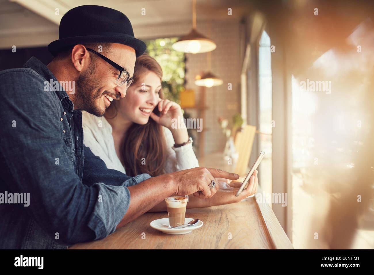 Sonriente joven pareja en una cafetería con equipo con pantalla táctil. El hombre y la mujer joven en Imagen De Stock