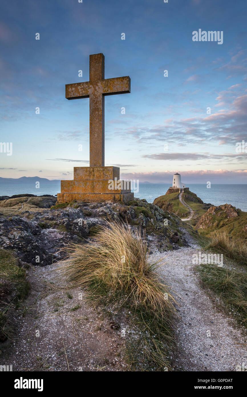 St Dwynwen's Cross y el faro en la isla Llanddwyn, Anglesey, al norte de Gales, Reino Unido al amanecer. Foto de stock
