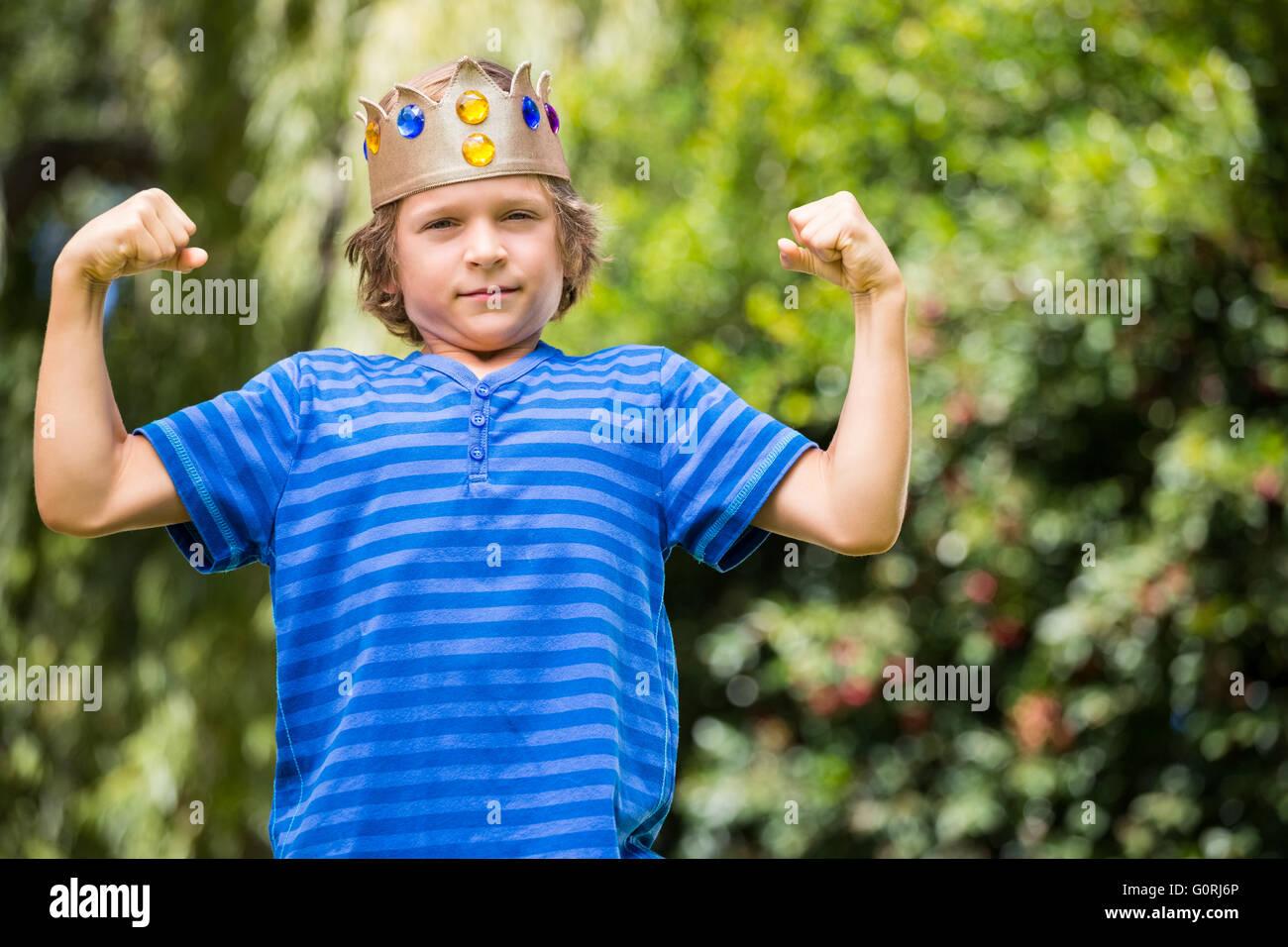 Chico lindo con una corona mostrando sus músculos Imagen De Stock