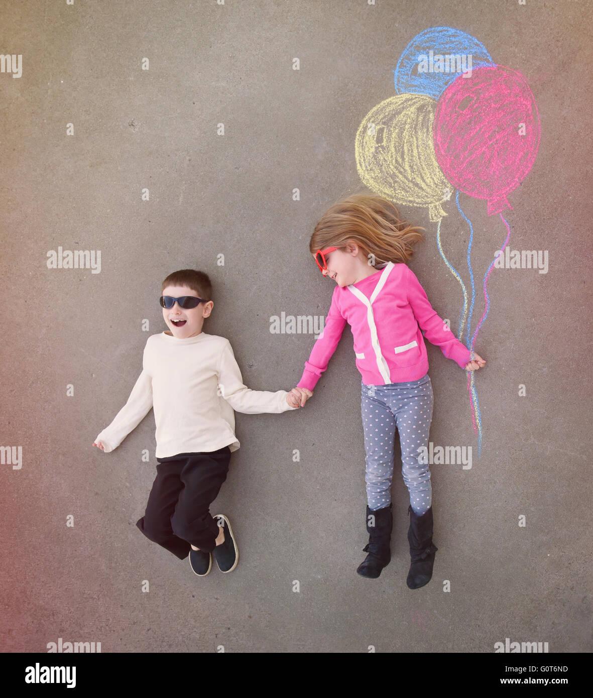 Los niños son tomados de las manos fuera con coloridos globos de tiza esbozado en cemento para un creativo, la artesanía o el concepto de juego Foto de stock