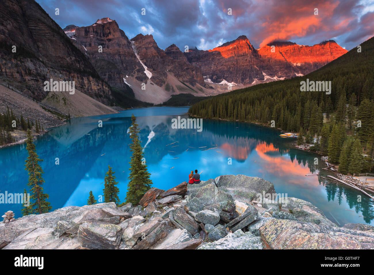 Una joven pareja en el lago Moraine por Sunrise. Parque Nacional de Banff, Alberta, Canadá. Imagen De Stock