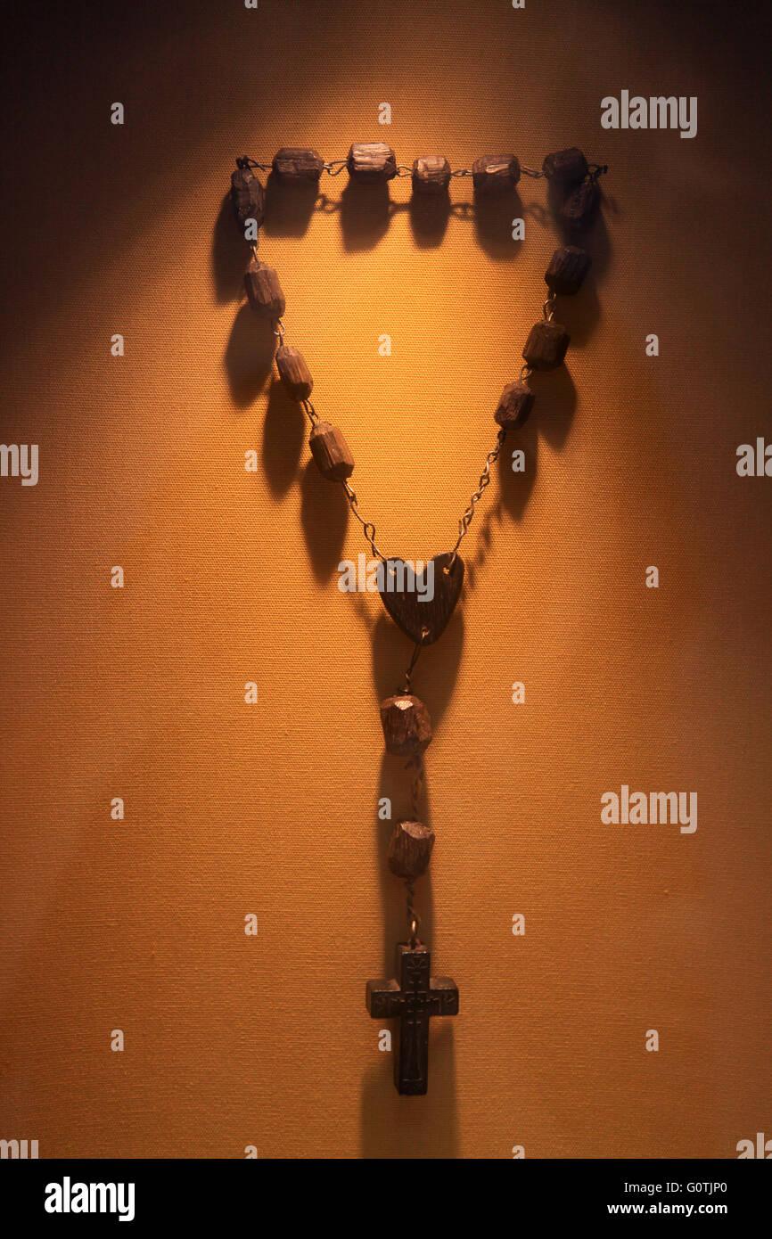 Rosario católico marrón de madera con luz de color naranja, colgando en la pared Imagen De Stock