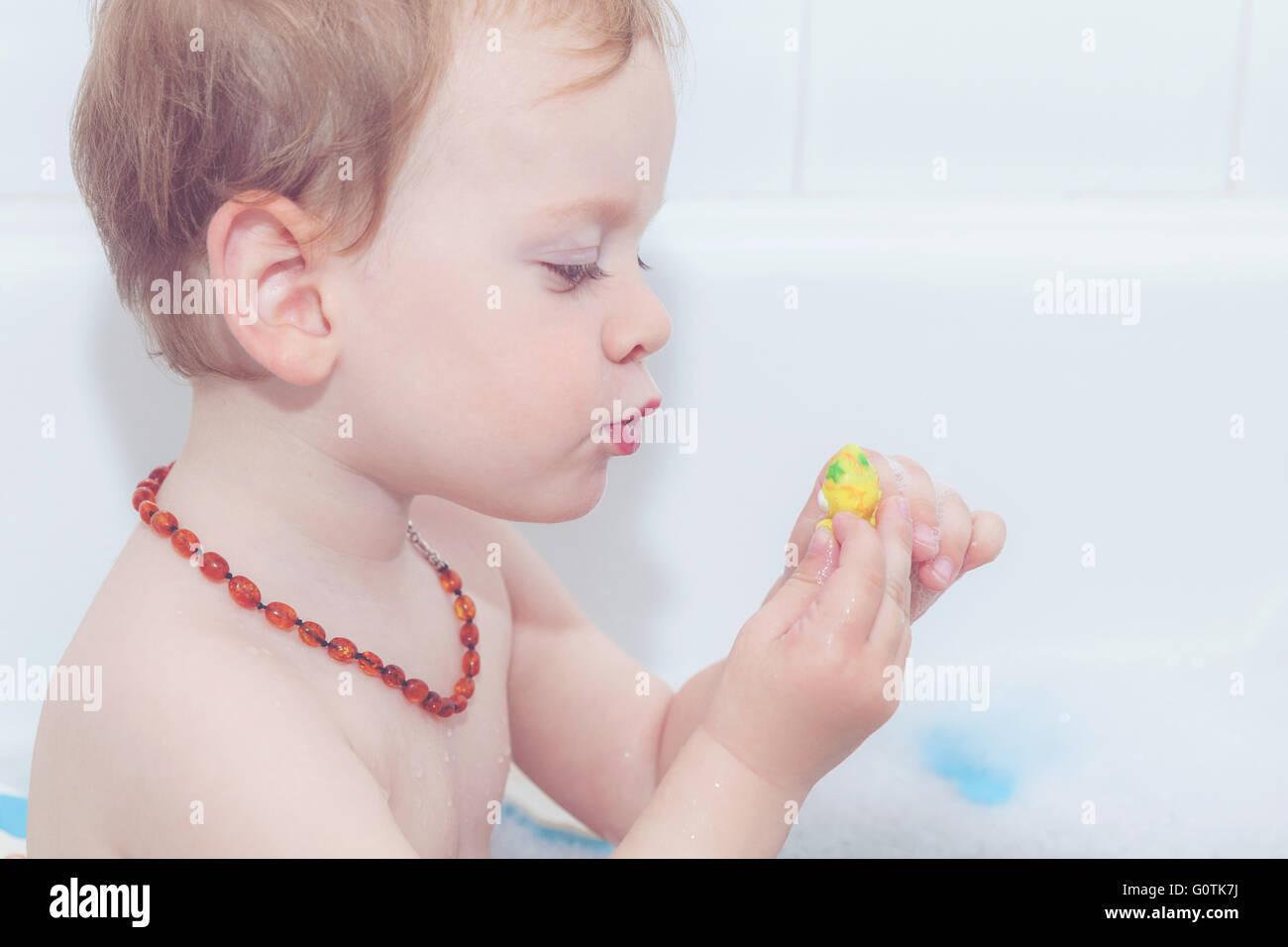 Retrato de un niño jugando con el juguete de plástico en el baño. Imagen De Stock