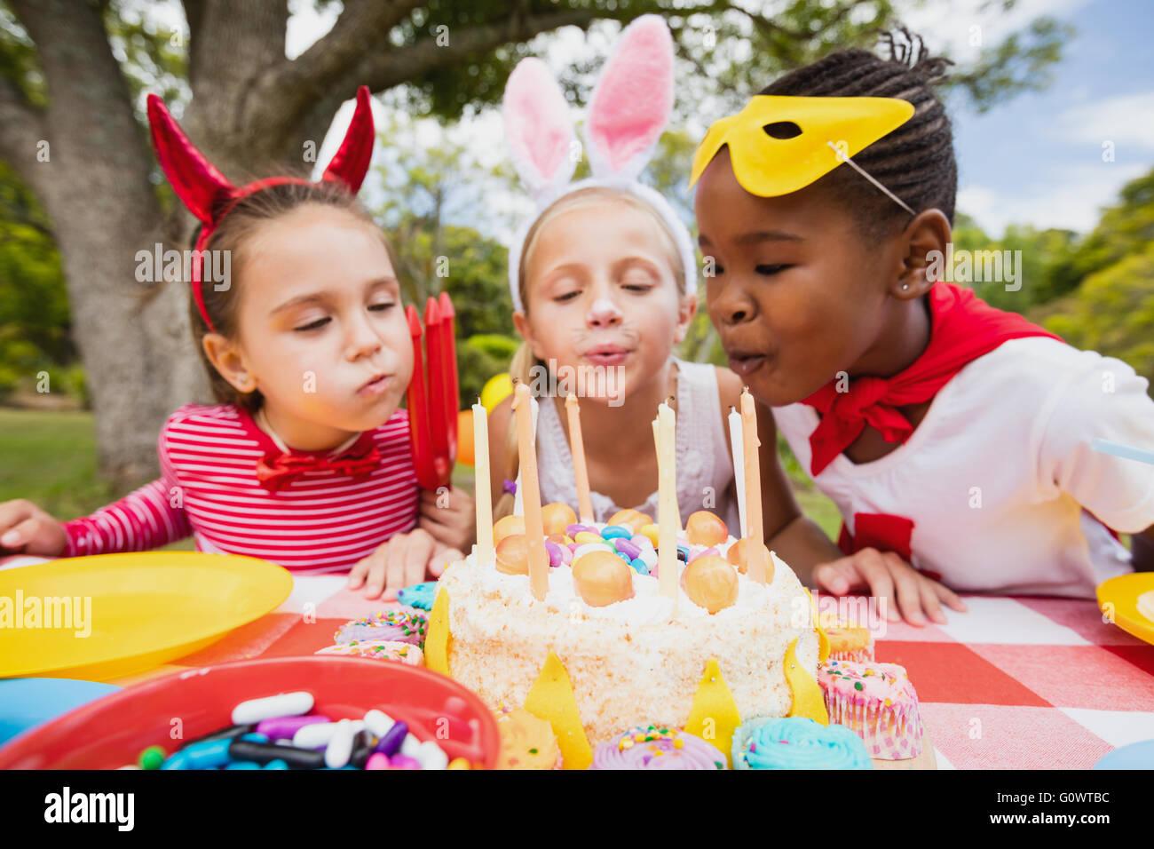 Tres pequeñas niñas soplando las velas de cumpleaños juntos Imagen De Stock
