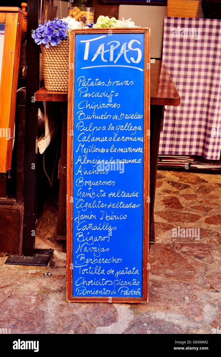La pizarra menú en un restaurante en España, con diferentes tapas españolas, como las patatas bravas o la tortilla de patatas Foto de stock