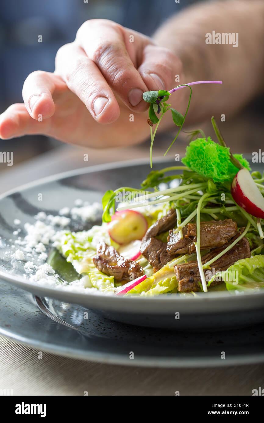 El chef de cocina del hotel o restaurante, sólo las manos. Él está trabajando en la hierba micro Imagen De Stock