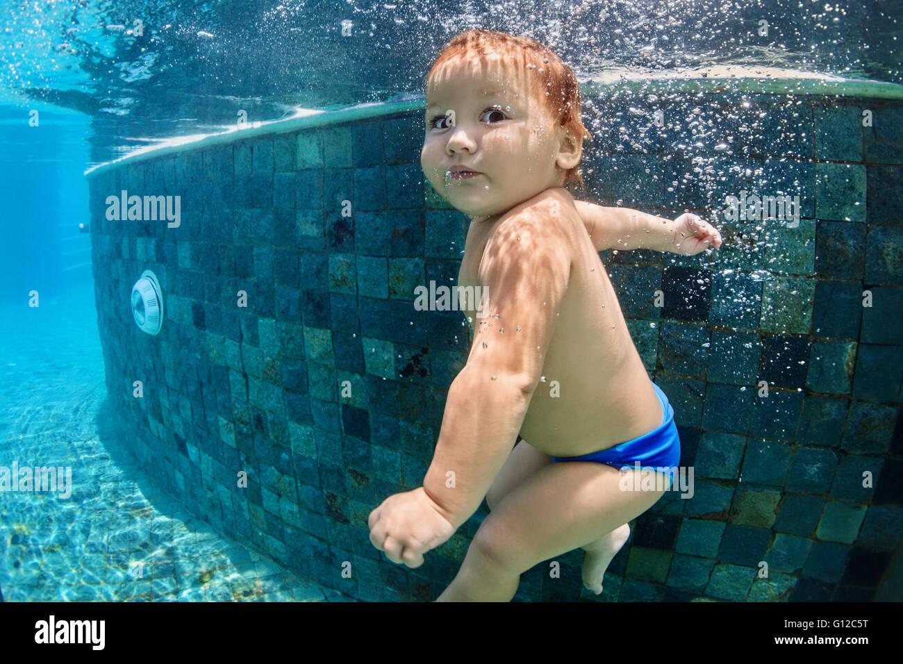 Gracioso foto del bebé activo nadar y bucear en la piscina con la diversión - Salto hacia abajo subacuático Imagen De Stock