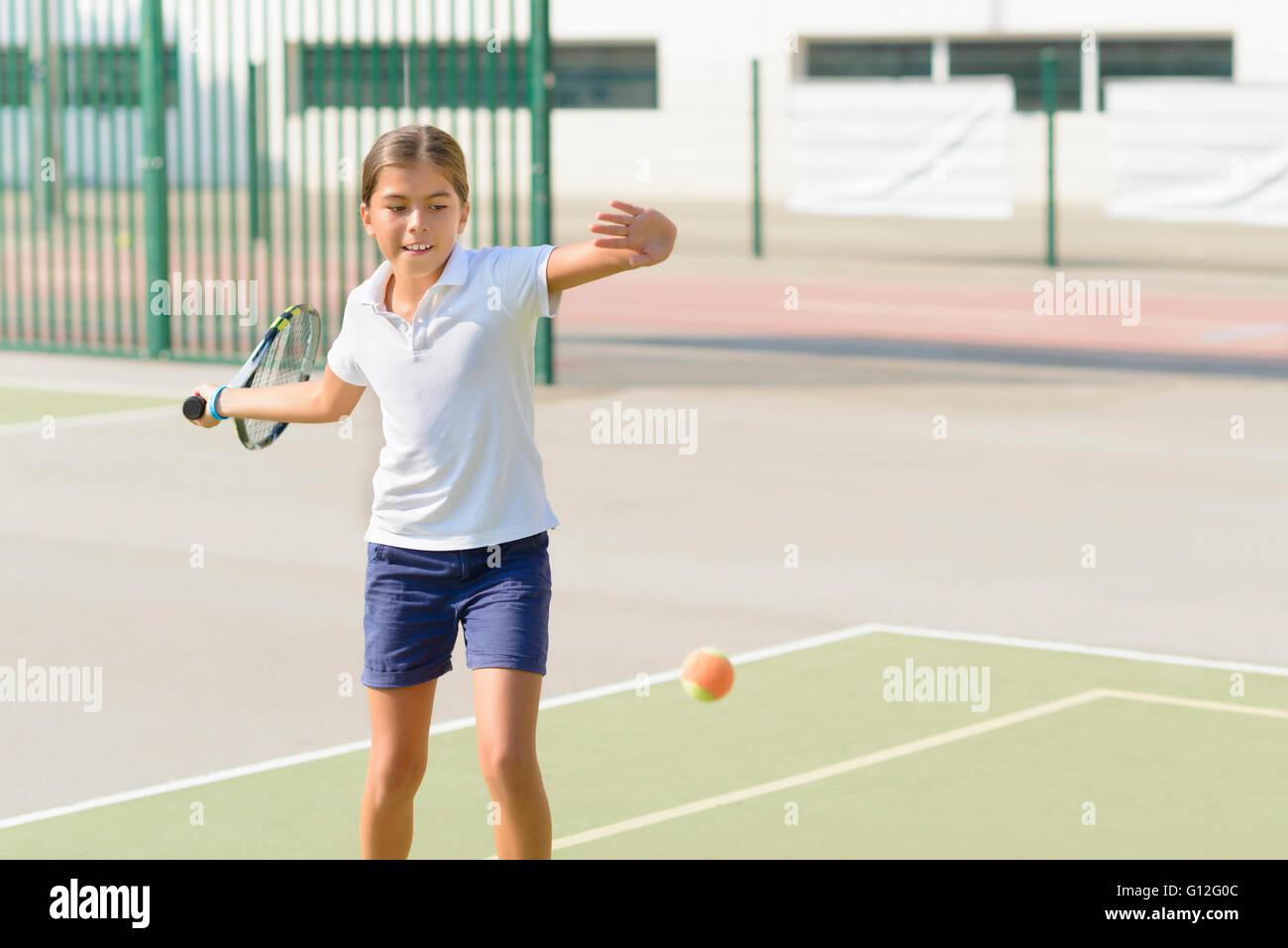 Hermosa niña jugando a tenis en la pista de tenis Imagen De Stock