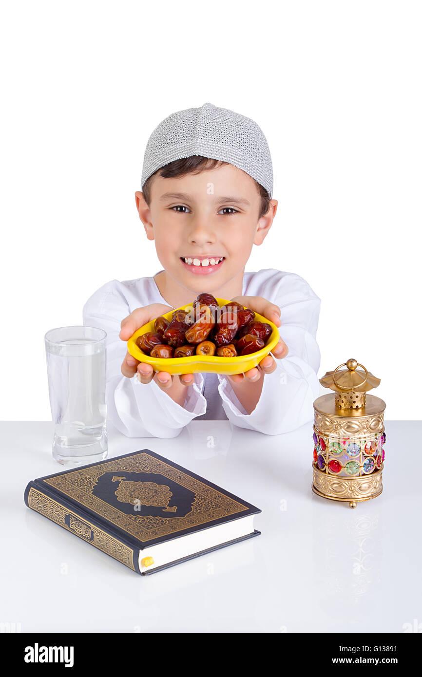 Poco chico musulmán sonriente mientras presentando un plato de fechas para iftar - mostrar generosidad de Ramadán Imagen De Stock